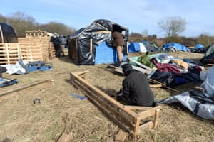 Migrants build shelters from plastic sheeting and wooden pallets