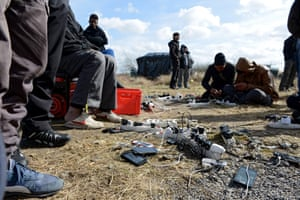 People gather to charge mobile phones at an electricity point