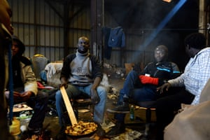 Migrants cook a meal inside an abandoned factory