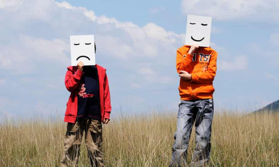 Boys in a field holding happy and sad facial expressions