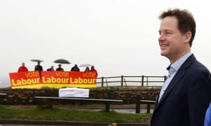 Nick Clegg at the unveiling of a Lib Dem election poster in Hyde, Cheshire, as Labour supporters look on.