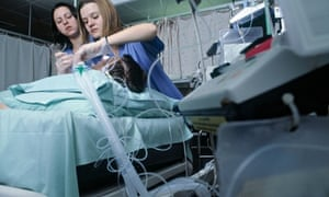 Spanish nurses put a patient on oxygen in an intensive care unit at an NHS hospital in Blackburn. Photograph: John Angerson /Alamy