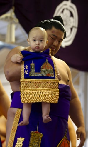 A sumo wrestler carries a baby before the 'Honozumo' ceremonial sumo tournament.