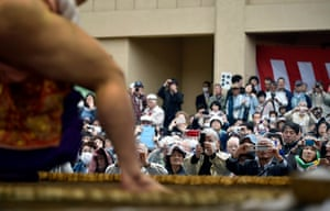 Spectators take pictures of a sumo wrestler ahead of a bout.