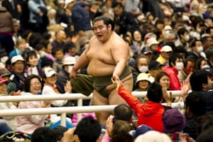 A sumo wrestler greets supporters after a bout.