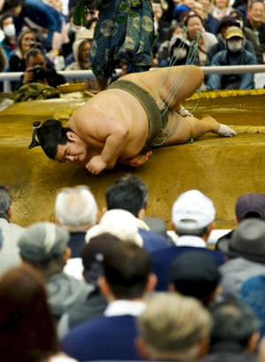 A sumo wrestler is thrown out of the ring.
