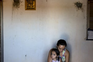 Marcia Xavier, daughter of late anti-pesticide activist Jose Maria Filho, who was shot 25 times with a 0.40 calibre pistol in April 2010 when driving home one night, sits with her mother outside their home in Limoeiro do Norte, Brazil. The framed writing on the wall reads 'God bless you in this house, may God be with you when you leave.'