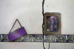 A photo frame and a purse hang on the wall of a house destroyed by an air strike near Sanaa airport. Air raids by a Saudi-led coalition again hit Houthi militia targets across Yemen this week. Arab states have said they will try to assemble a unified military force to combat common threats across the Middle East, as Yemen was described as being 'on the brink of the abyss' at the Arab League summit