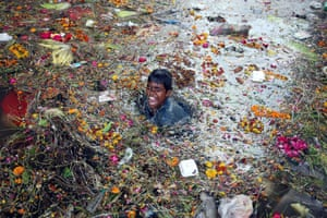 An Indian child searches for coins under the polluted waters of the river Tawi on the last day of NavratrI, a Hindu festival in Jammu