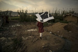 A boy holds his kite at a slum on the outskirts of Islamabad, Pakistan