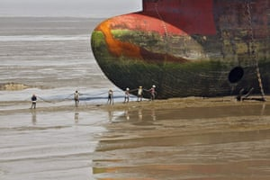 Workers carry a rope line to fasten a decommissioned ship at the Alang shipyard in  Gujarat, India. The European Union plans to impose strict new rules on how companies scrap old tankers and cruise liners, which are run aground and dismantled on beaches in South Asia. However the practice in India, Bangladesh and Pakistan, hazardous for humans and the environment, will still be hard to stop. Depending on raw material prices, ship owners can make up to $500 per tonne of steel from an Indian yard, compared with $300 in China and just $150 in Europe