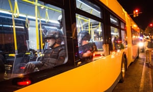 Riot police are brought in on a public bus to monitor protests in Baltimore.