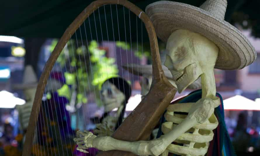 A skeleton playing a harp in an Altar of the Dead at in Mexico City as part of the Day of the Dead celebration.