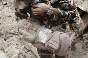 Four-month-old boy Sonit Awal is held up by Nepalese army soldiers after being rescued from the rubble of his house in Bhaktapur after 20 hours