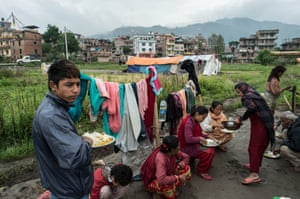 Earthquake victims have lunch near their makeshift tent shelter
