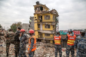 Members of the army stand on the rubble of collapsed buildings near Gangabu