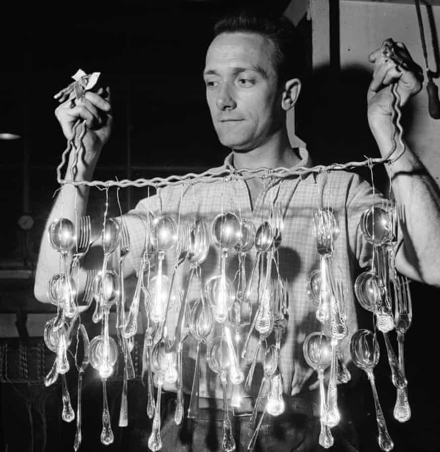 A worker hanging out newly silver-plated forks and spoons to dry at a Sheffield steel cutlery factory, 1959.