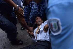 Maldives police try to move former president Mohamed Nasheed as he arrives at court in Male.