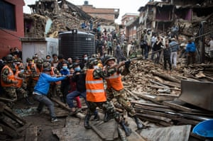 Nepalese soldiers and civilians try to pull down a section of severely damaged wall in danger of collapsing in Bhaktapur