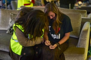 A local crisis councillor comforts a distraught woman at London Stansted airport after around 120 British people were evacuated from Nepal on the return journey of a UK aid flight