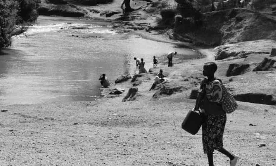 Kenyans collect water from contaminated river.