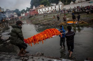 The body of an earthquake victim is carried before a cremation ceremony at Pashupatinah temple