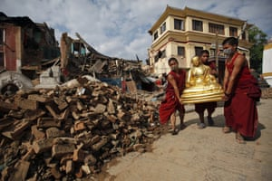 Buddhist monks salvage a statue from the monastery near the Swayambhunath stupa