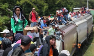 Central American immigrants ride north on top of a freight train, known as 'la bestia', near Juchitan, Mexico.