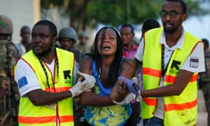 A woman is rescued from the building where she had been held hostage after a fierce gunfight between Kenyan soldiers and al-Shabaab attackers at  Garissa University.
