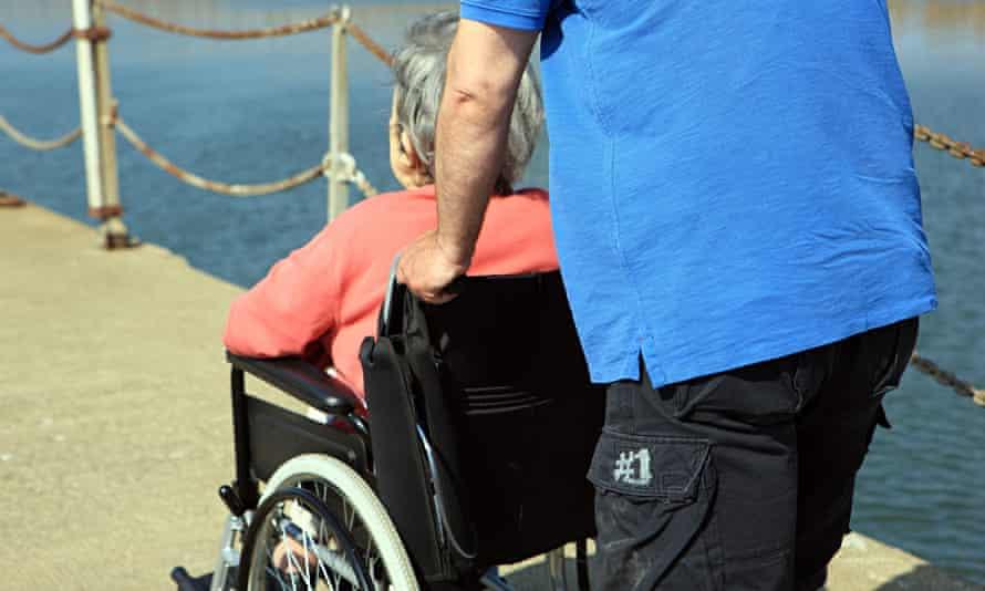 Man pushing an elderly lady in a wheelchair
