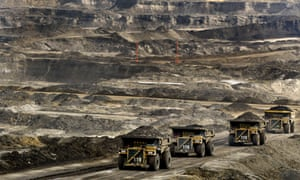 "Mining lorries carry loads of tar sands in Alberta, Canada. One climate scientist warned that it would be ""game over"" for efforts to stop global warming if Canada's tar sands were fully exploited."