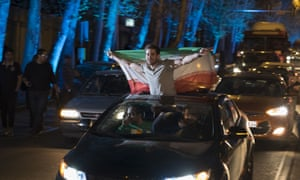 An Iranian man flashes victory signs while holding an Iran flag to celebrate Iran's nuclear agreement with world powers in Lausanne.