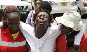 Red Cross staff console a woman in Nairobi after she viewed the body of a relative killed in Thursday's attack.
