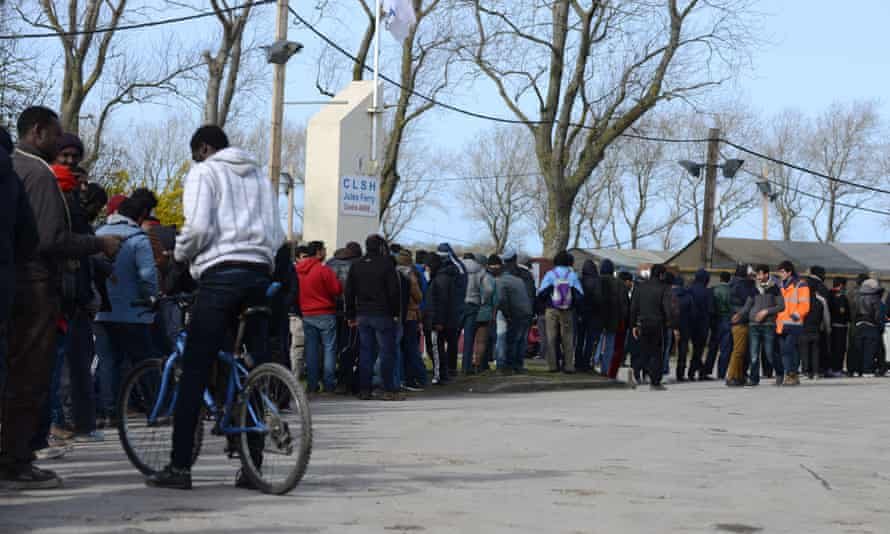 People queue outside the Calais camp for food.