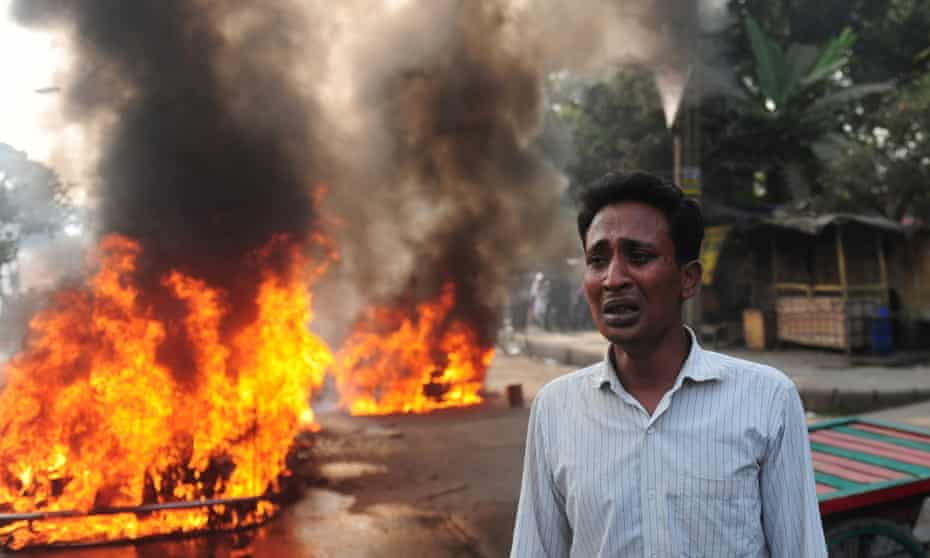 A Bangladeshi man stands near a burning car set on fire by demonstrating Jamaat-e-Islami supporters following the execution of Abdul Quader Molla in 2013. The supreme court has now upheld the death sentence for fellow islamist Mohammad Kamaruzzaman.