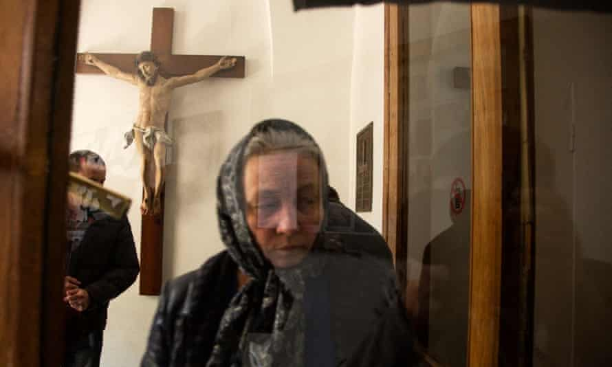 A woman attends mass.