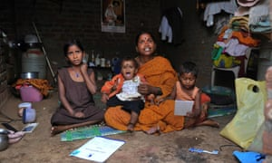 Kommani Lalitha poses with her daughters and her microfinance 'loan recovery book' at her residence in the Ranga Reddy District, in the outskirts of Hyderabad, India. Microfinance, one of the most widely touted tools for alleviating poverty, has come under fire recently.