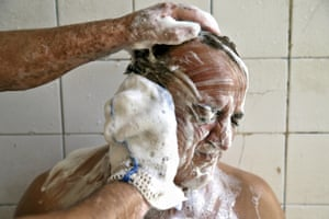 A man bathes with the help of a bathhouse worker at the Mohammadi public bathhouse in Yazd, Iran. In the old days, the bathhouses functioned more than just a place to clean up, shave or get a massage from a  dallak, a masseuse who uses a mitt to scrub and exfoliate a client's body; people gathered in the humid air to discuss current events and debate ideas.