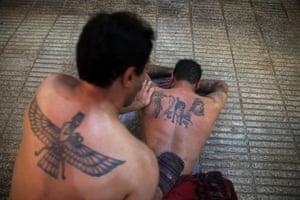 Bathhouse worker Omid Riahi, 39, scrubs a man to remove dead skin, at the Ghebleh public bathhouse, in Tehran, Iran.