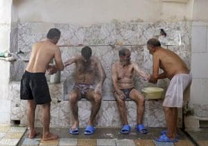 Bathhouse workers Reza Bagheri, 75, and Heidar Javadi, 39, help two men bathe at the Setareh public bathhouse, in Yazd, Iran.