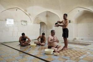 Heidar Javadi, 39, a bathhouse worker pours warm water on a man at the Setareh public bathhouse, in Yazd, Iran.