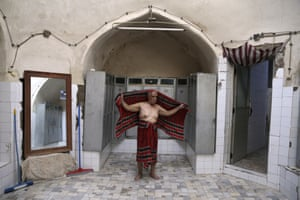 Ali Tayyeb, 70, a bathhouse worker, dries himself at the end of his workday, at the Islam public bathhouse, in Yazd, Iran.