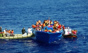 A photo taken by the Migrant Offshore Aid Station shows the Italian Navy (let) helping refugees to climb on their boat in the Mediterranean.