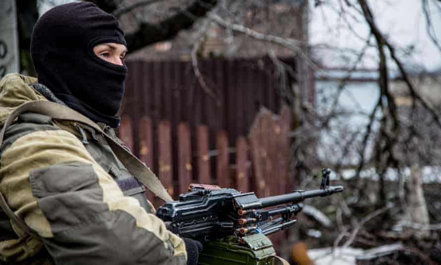 An armed separatist fighter stands in front of destroyed house in the Spartak neighbourhood of Donetsk.