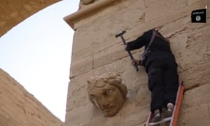 A militant destroying a statue on a wall at Hatra.