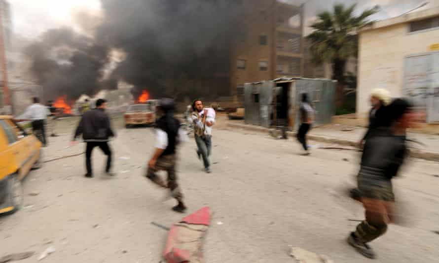 A man runs with an injured child during alleged shelling by Syrian government forces in Idlib city.