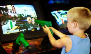 A boy aims a toy gun at an arcade game. But could access to violent games constitute neglect?