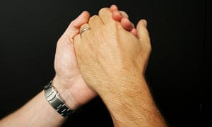 Two men's hands, one with a wristwatch on the arm