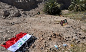 An Iraqi flag covers a site believed to be a mass grave of soldiers killed by Isis.