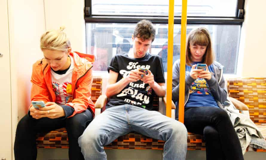 Three people absorbed in their phone on the tube.